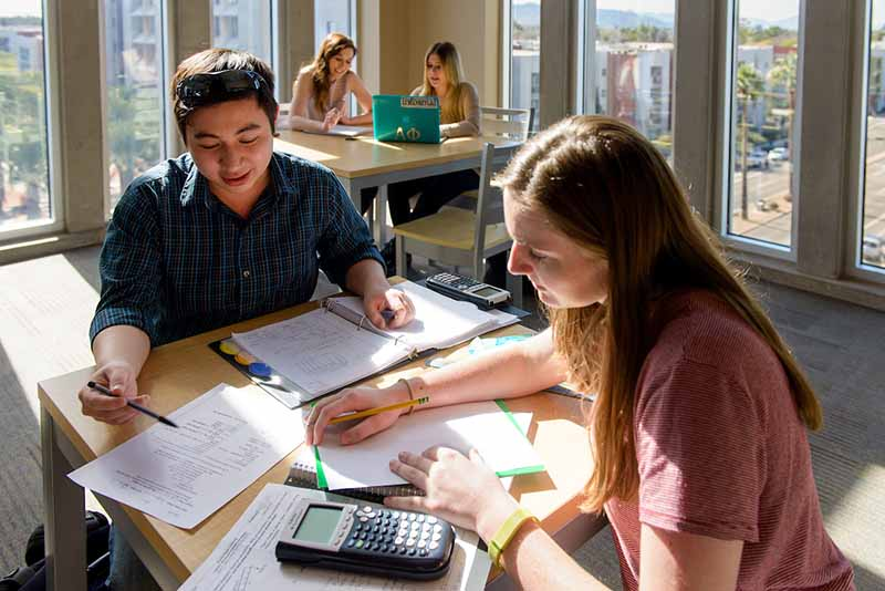 Male and female ASU students studying together in a sunny room