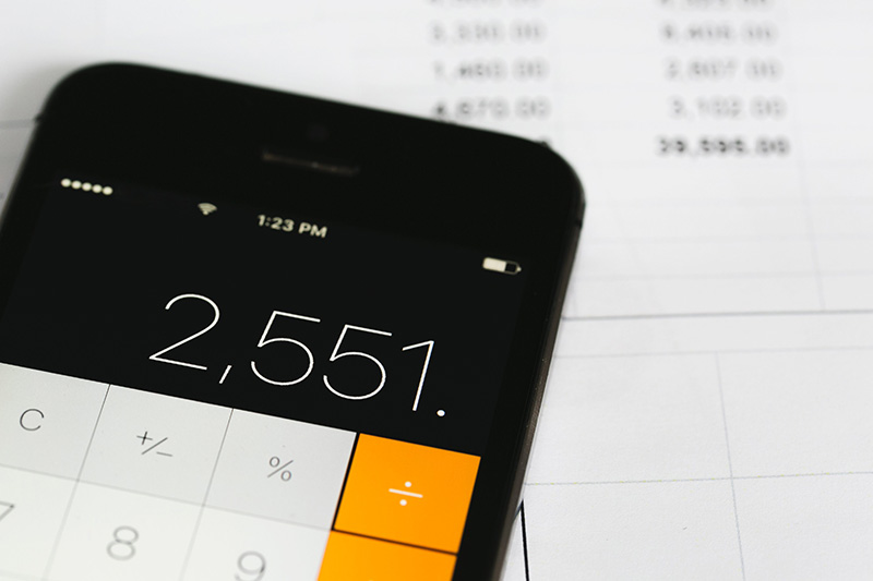 An iPhone calculator over a white spreadsheet