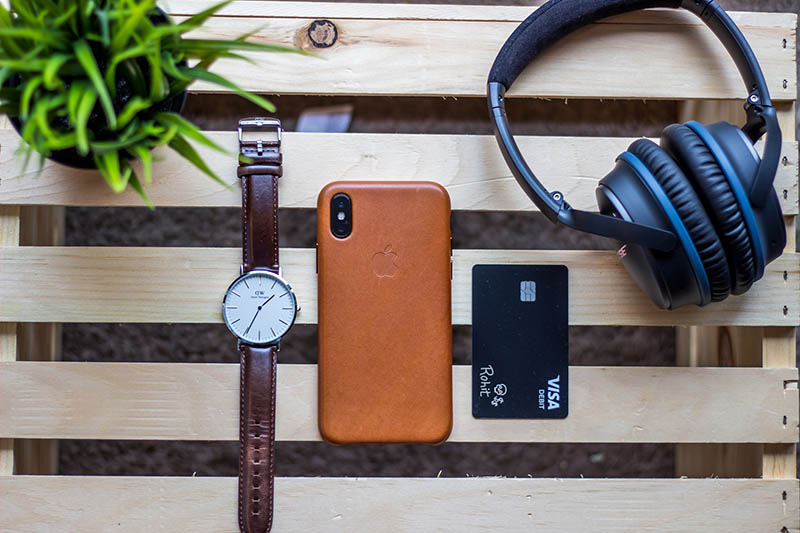 a table with a watch, iPhone, credit card and headphones