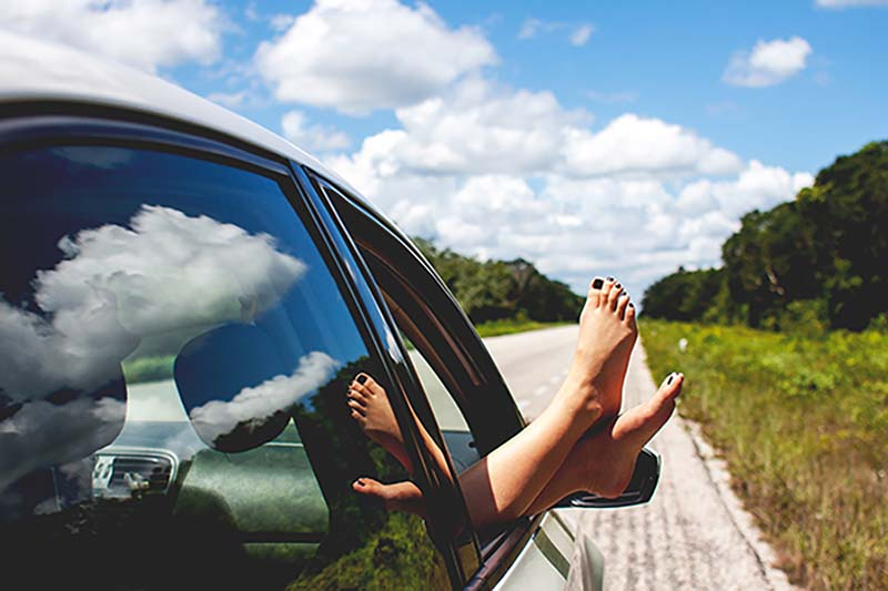 An open road with feet sticking out of a car window