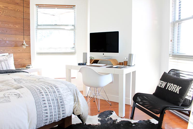 A dorm room with light colors, a desktop computer and a bed with white sheets