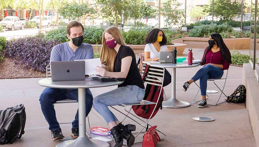 students making friends safely distanced on campus