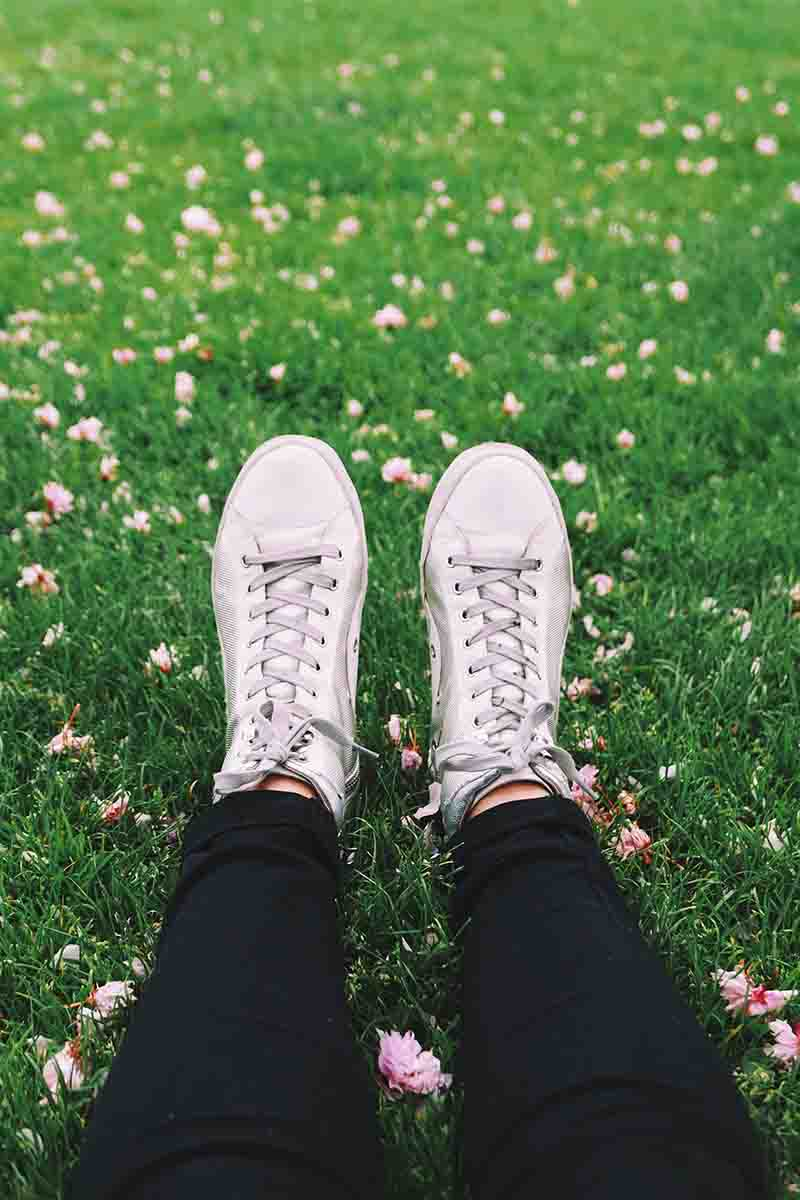A womans legs in black pants and white shoes on green grass