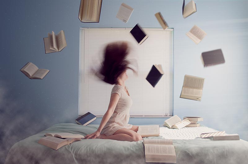 girl is sitting on a bed in a dorm room books are floating in the air around her and she's whipping her hair up