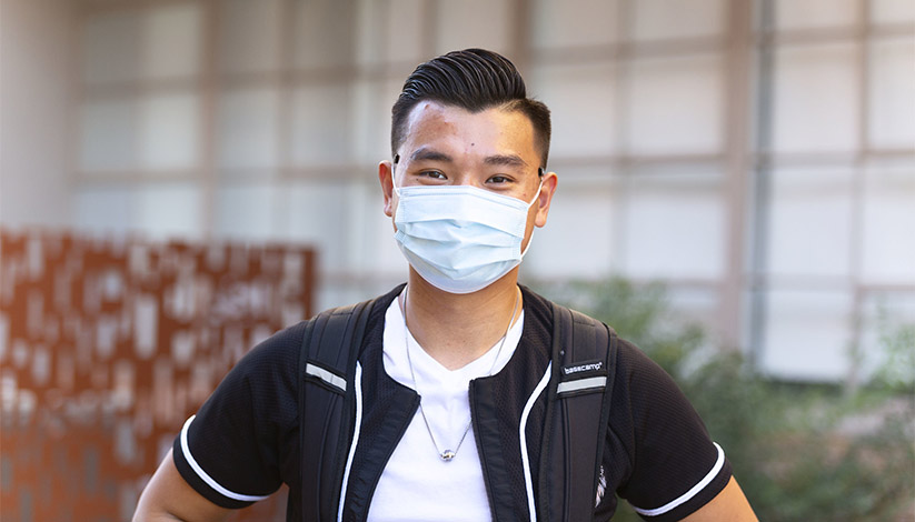 Student standing and looking at the camera while wearing a face mask.
