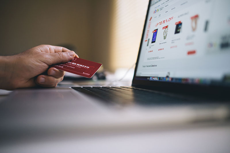 Man holding credit card next to laptop computer as if to use it for shopping