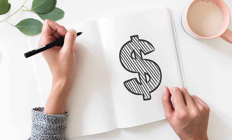 Person drawing in a white notebook. Drawing is of a dollar sign