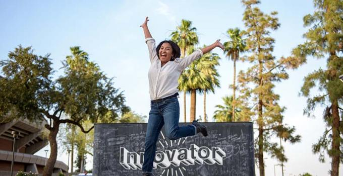 "A girl leaping enthusiastically in front of a chalkboard that says ""innovation"" and trees are behind it"