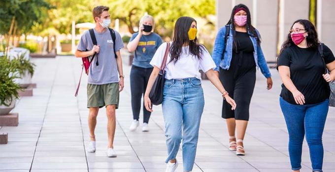 students and friends walking through campus together with face masks on