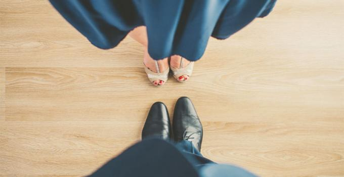 two pairs of feet facing each other. One a woman with ballet flats and a skirt and the other a man's dress shoes.