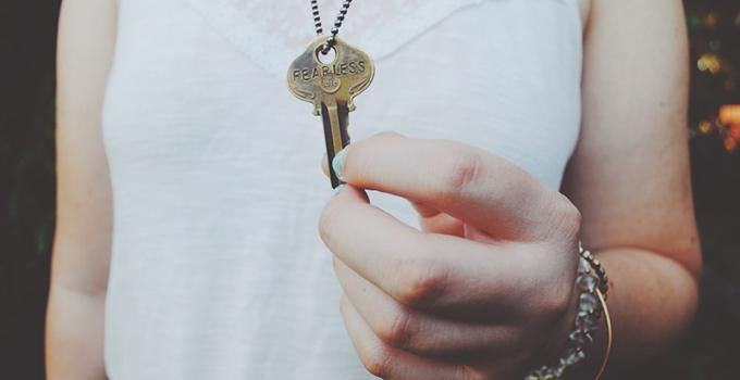 "Woman holding a key to a new apartment. The key is stamped with the word ""fearless"""