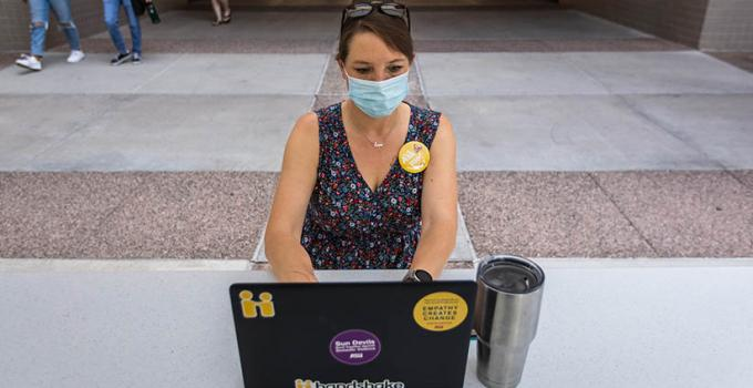 ASU student on campus wearing a mask and working on her laptop