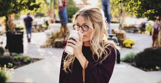 Blonde girl drinking coffee in a beautiful outdoor city