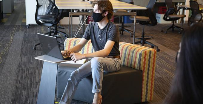 student sitting at desk wearing a face mask and on a laptop