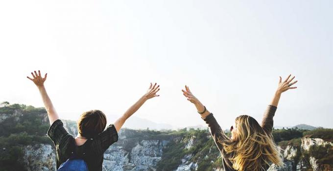 two girls with their hands in the air embracing life