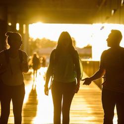 three students walking in Coor Hall in silhouette into the sun