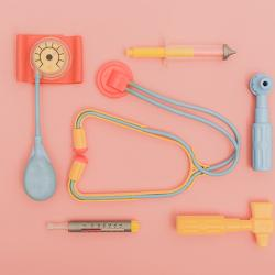 Image shows pastel plastic doctor's tools laying flat