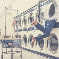 Student digging deep into laundry machine at laundromat