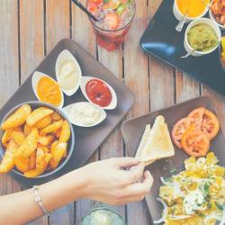 A bunch of appetizers on a table with a hand grabbing for a chip