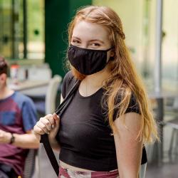 female first year student wearing a face mask and holding a backpack on ASU campus