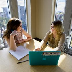two female student are sitting together working on homework together.