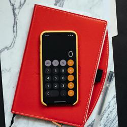 calculator-sitting-on-red-folder-on-stack-of-paper-on-black-table