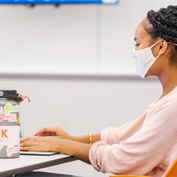 A student sitting in her seat in an ASU classroom, wearing a face mask and working on a laptop with a water bottle next to her.