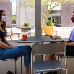 Two students chatting over a table outside on the ASU campus