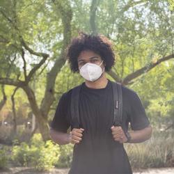 student on the tempe campus wearing a facemask and backpack