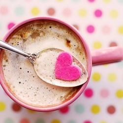 Pink mug on a light shades of pink polka dot mat. The mug is filled with hot chocolate and a spoon holds up a pink heart from the mug
