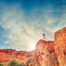 Girl on top of red rock mountains happy