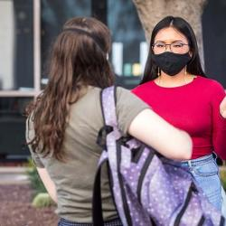 A girl is talking to another person on the ASU campus wearing a face mask.