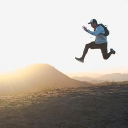 Image shows a male jumping at the top of a hill