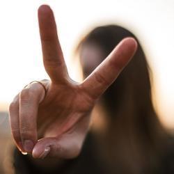 girl holding up a peace sign with her fingers her face is blurred out of focus in background.