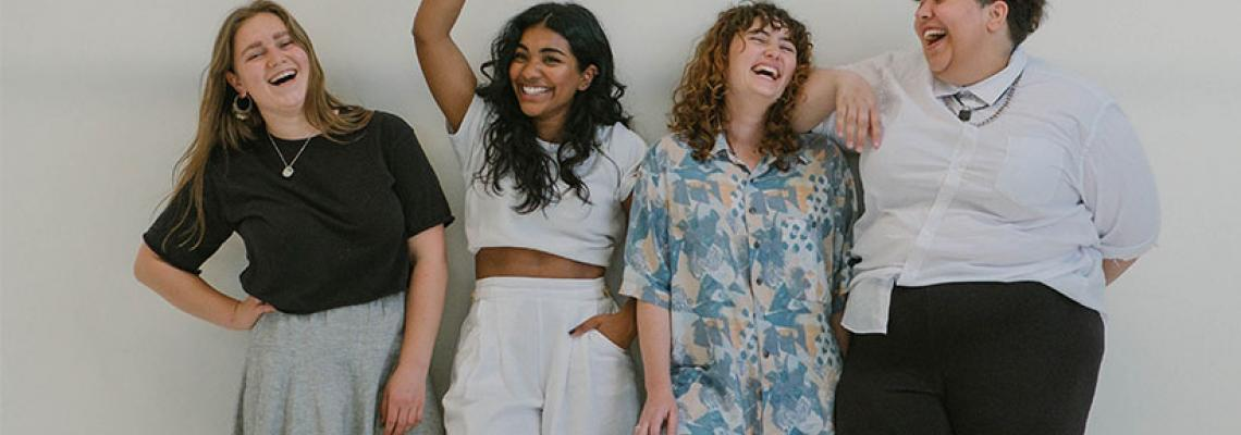 group-of-girl-friends-stands-in-a-line-laughing